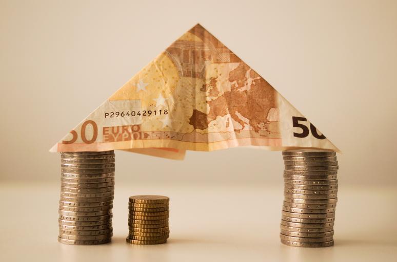 dva sloupy z mincí, které drží bankovku a ta dělá jakoby střechu